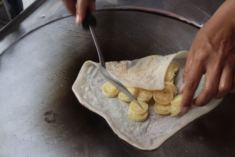 Close-up of person preparing banana crepe