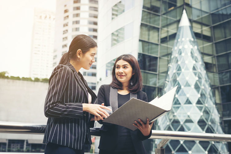 Smiling businesswoman with folder looking at colleague while standing against buildings
