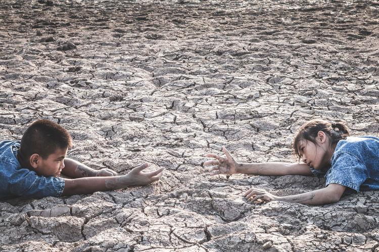 Siblings lying on cracked land