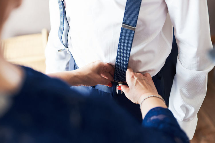 Midsection of mother adjusting suspenders on son during wedding ceremony