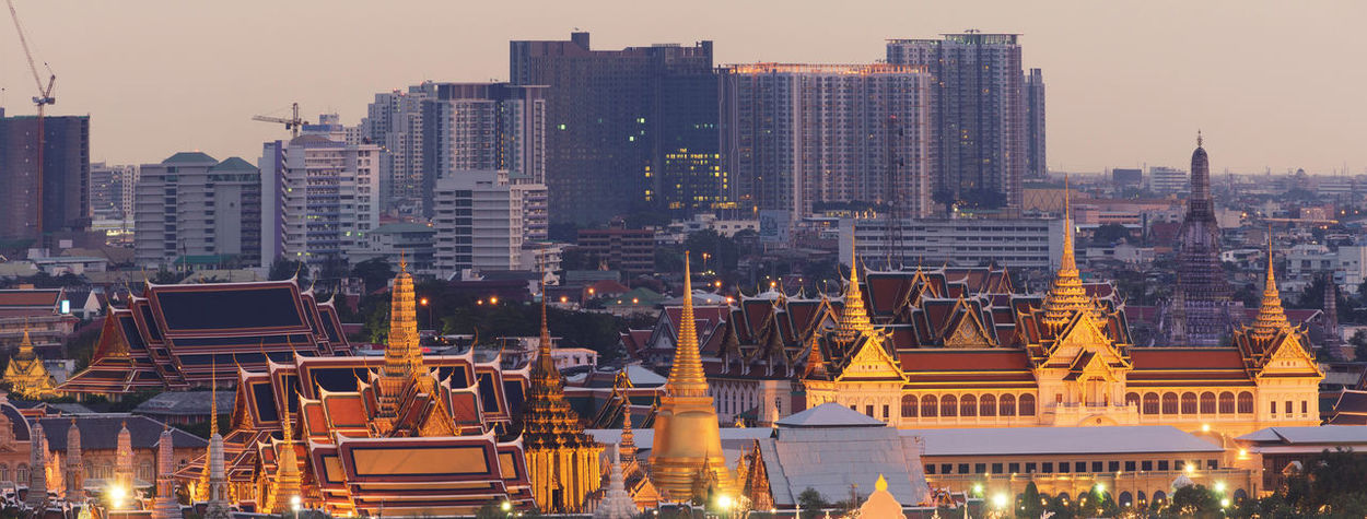 The Emerald Buddha at Sunset, Bangkok, Thailand Emerald Buddha Temple Grand Palace Bangkok Thailand Architecture Building Exterior Built Structure City Cityscape Clear Sky Day Illuminated Modern No People Outdoors Sky Skyscraper Sunset Travel Destinations Urban Skyline