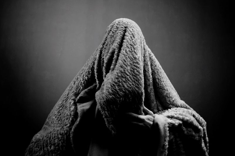 Man wrapped in blanket against wall