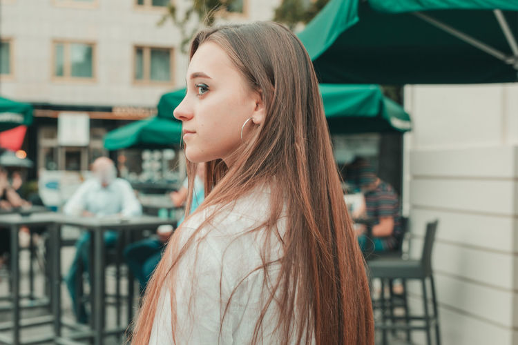 Close-up of young woman standing by sidewalk cafe