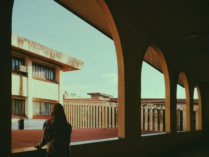 Woman Standing In Corridor Against Sky