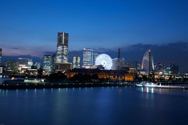 Illuminated cityscape against blue sky