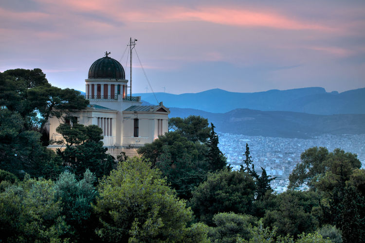 Athens with the National Observatory in the foreground. Architecture Athens, Greece Cloud Cloudy GREECE ♥♥ Sunset_collection Trees Architecture Athens Building Exterior Built Structure Day Dome Greece Mountain Nature Neoclassical No People Outdoors Sky Sunset Sunsetporn Sunsets Travel Destinations Tree Colour Your Horizn