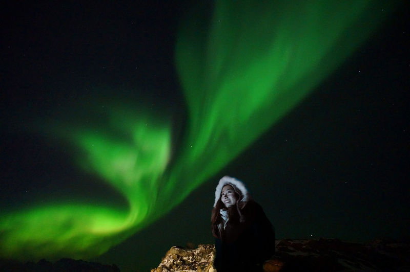 Low Angle View Of Woman Standing Against Aurora Borealis At Night