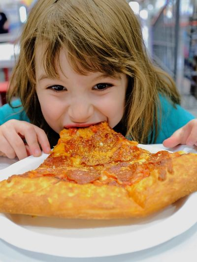Close-up portrait of girl eating pizza in restaurant