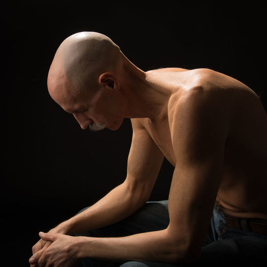 Mature man with shaved head against black background