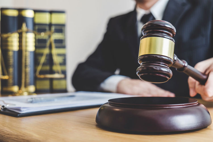Midsection Of Lawyer Holding Gavel At Office