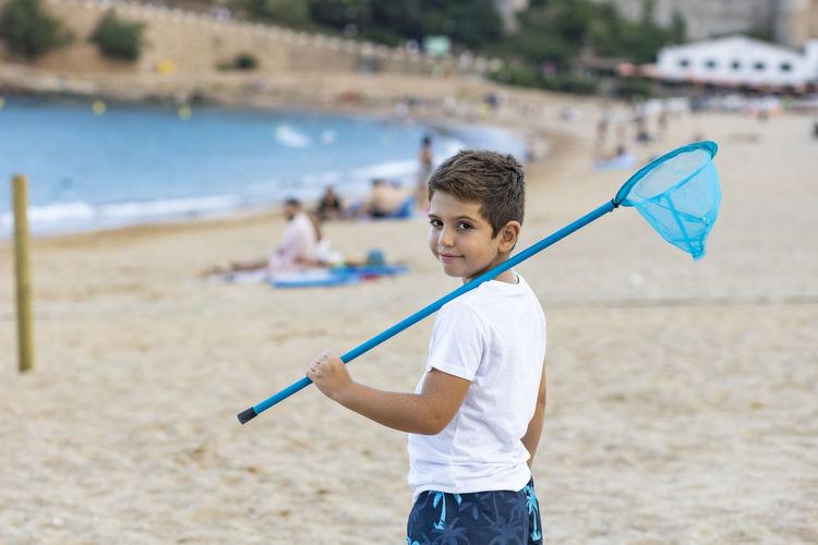 Portrait of boy holding net standing on beach