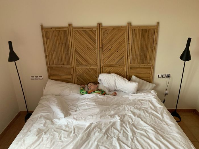 Alone Sleeping Children Childhood Boy Bed Bedroom Furniture Indoors  Domestic Room Pillow Lighting Equipment Home Interior No People Relaxation Electric Lamp Sheet Linen Comfortable Textile Night Table White Color Lifestyles Day Cozy