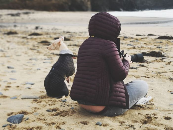 woman and her dog. Bedlington Whippet Photographing The Photographer Warm Clothing On The Beach Personal Perspective Sitting Down Friendship Pets Togetherness Beach Full Length Sitting Dog Bonding Sand Mixed-breed Dog Human Connection 2018 In One Photograph