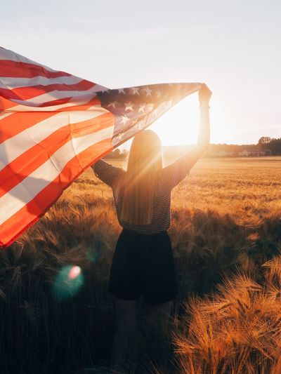 Rear view of woman standing on field against sky during sunset holding us flag
