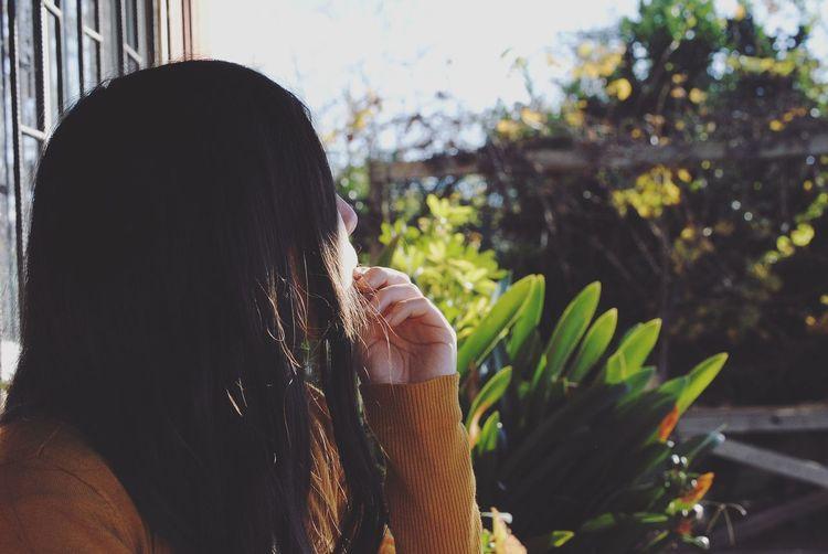 Side view of thoughtful woman at backyard