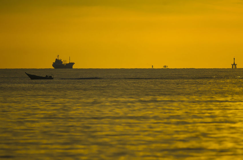 Silhouette objects. Natural yellow cor around the beach in the evening Beauty In Nature Mode Of Transportation Nature Nautical Vessel No People Orange Color Outdoors Sailboat Sailing Scenics - Nature Sea Ship Sky Sunset Tranquil Scene Tranquility Transportation Travel Water Waterfront