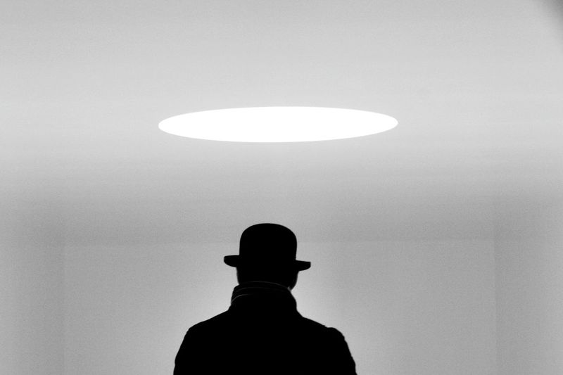 Rear view of man wearing hat standing in illuminated room