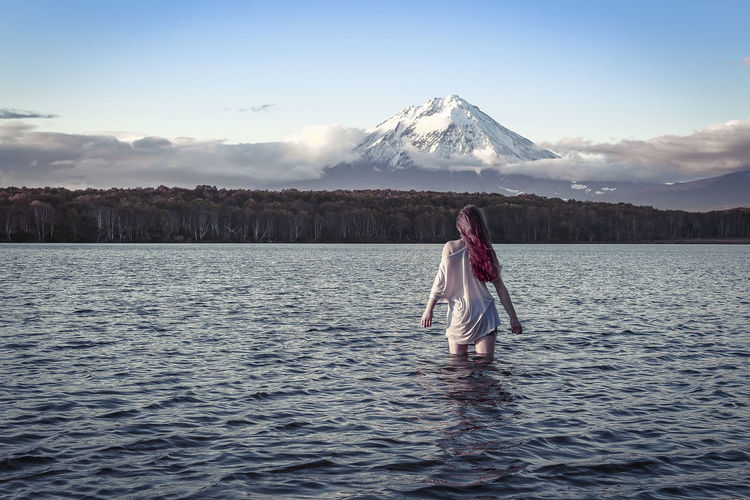 Rear view of woman standing in lake against snowcapped mountains