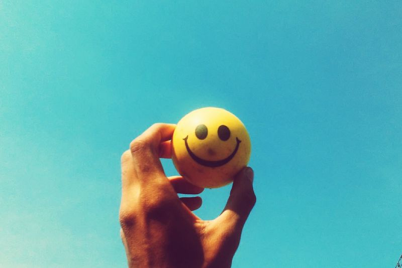 Close-Up Of Hand Holding Yellow Smiley Face Ball Against Blue Sky