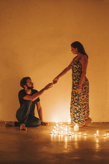 Full length of couple standing against wall