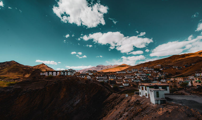 Houses on mountain against blue sky