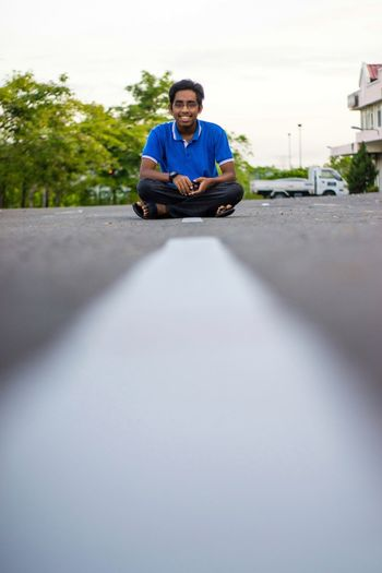Portrait of young man sitting on car