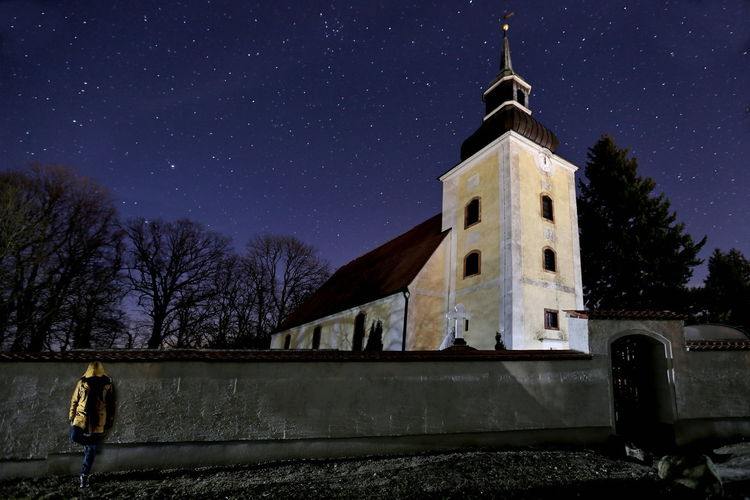 Man leaning on wall on church against sky at night