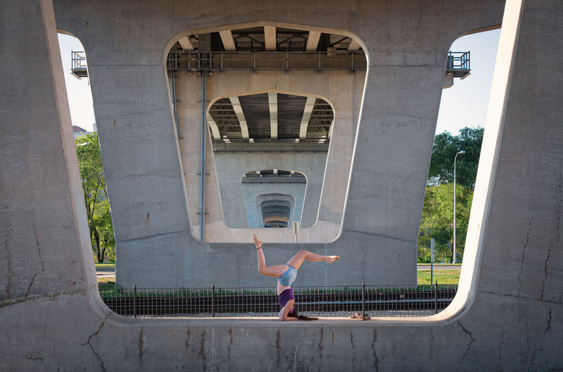 Full length of woman exercising under bridge