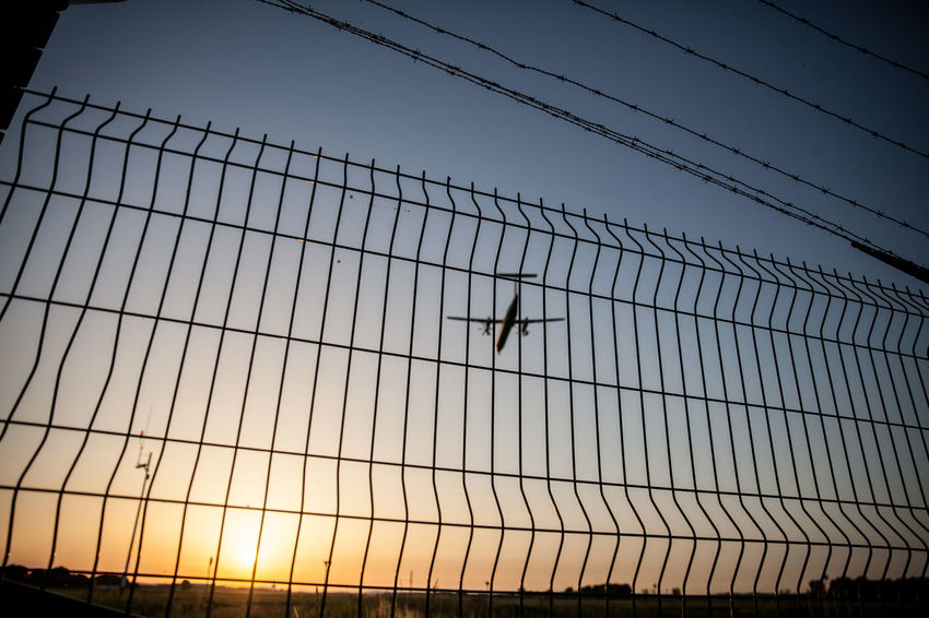 Airplane landing on sunset. Budapest, Hungary Air Airplane Airport Airport Fence Blue Cable Day Fence Low Angle View Nature Night No People Orange Color Outdoors Runway Silhouette Sky Sunset