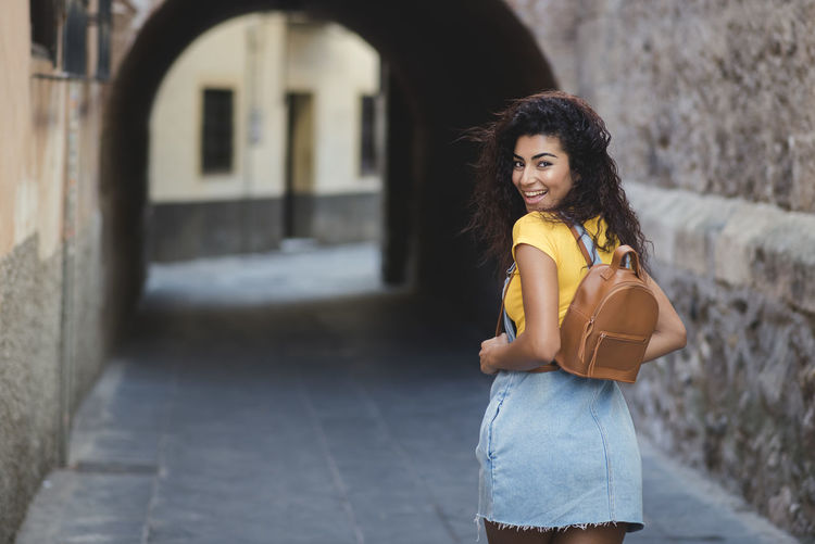 beautiful mixed girl with backpack walking happy in the street Architecture Beautiful Woman Beauty Building Exterior Built Structure Focus On Foreground Hair Hairstyle Lifestyles Long Hair Looking At Camera One Person Outdoors Portrait Real People Smiling Standing Three Quarter Length Women Young Adult Young Women