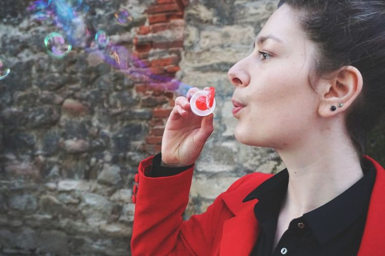 Close-up of young woman blowing bubbles against wall