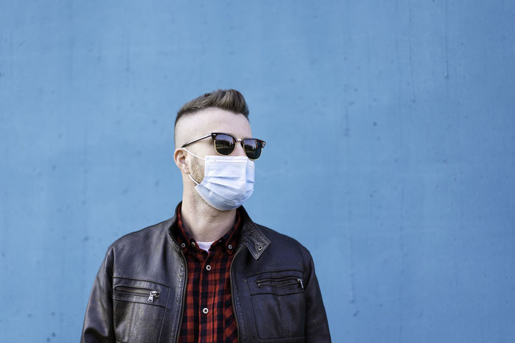 Man wearing mask standing against blue wall