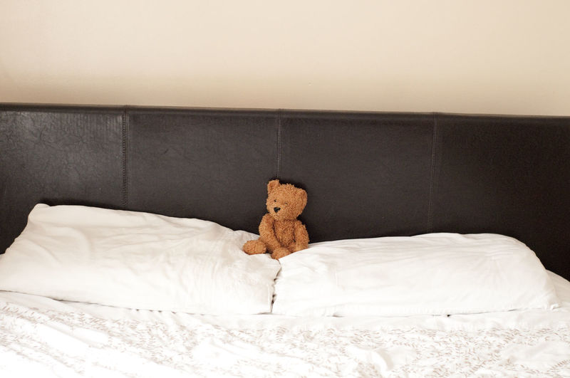 Close-up of teddy bear on bed at home