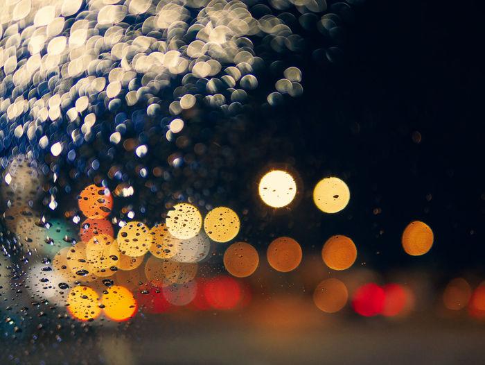 Defocused image of illuminated lights on wet glass