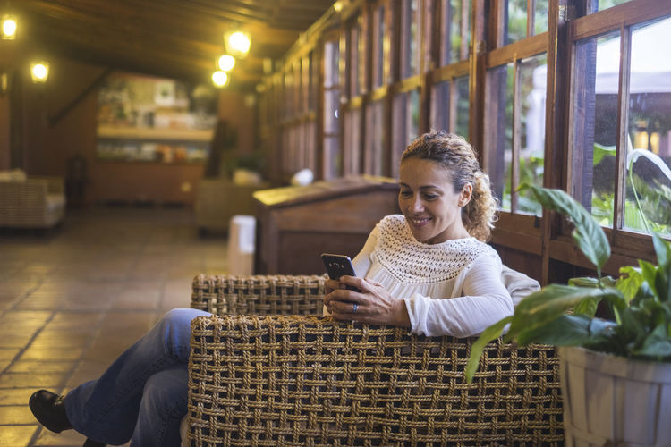 Smiling Mature Woman Using Mobile Phone While Sitting On Sofa At Home