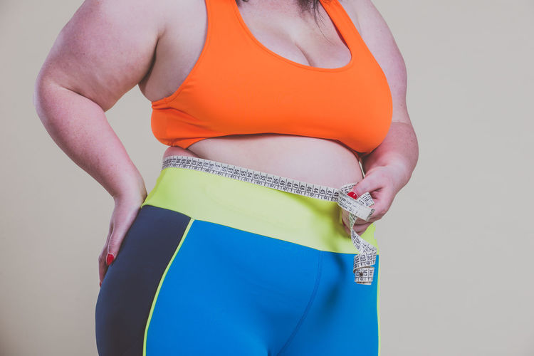 Midsection of woman holding tape measure against colored background