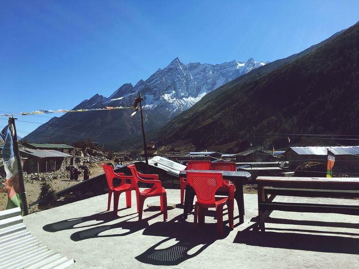 View of chairs on mountain against clear sky