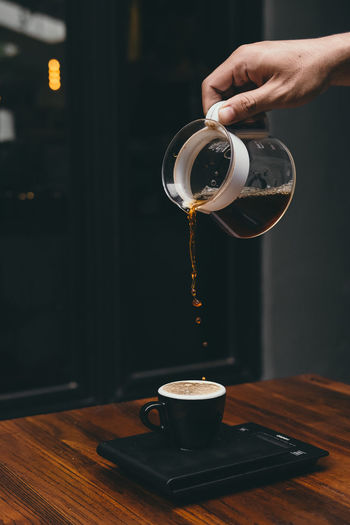 Cropped hand of person pouring coffee in cup on table