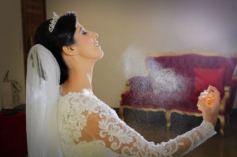 Side view of bride spraying perfume in room