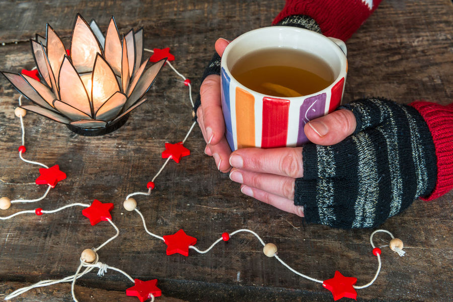 Female hands holding a cup of hot drink on rustic wooden table, close-up Beverage Christmas Colors Concept Drink Female Hands Food And Drink Hands Hold Holding Hot Hot Drink Mittens Warm Clothing Warming Up Weather Weathered Winter Wooden Background Wormth
