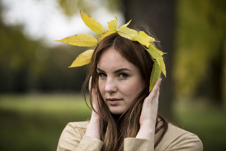 Close-up portrait of beautiful young woman holding leaf crown