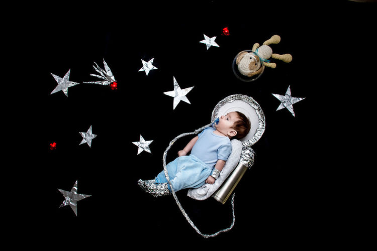 Baby With Astronaut Costume Against Black Background
