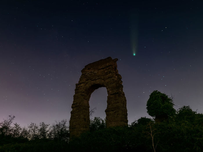 The comet neowise in the sky of rome, against the background of the ruins of an roman aqueduct.