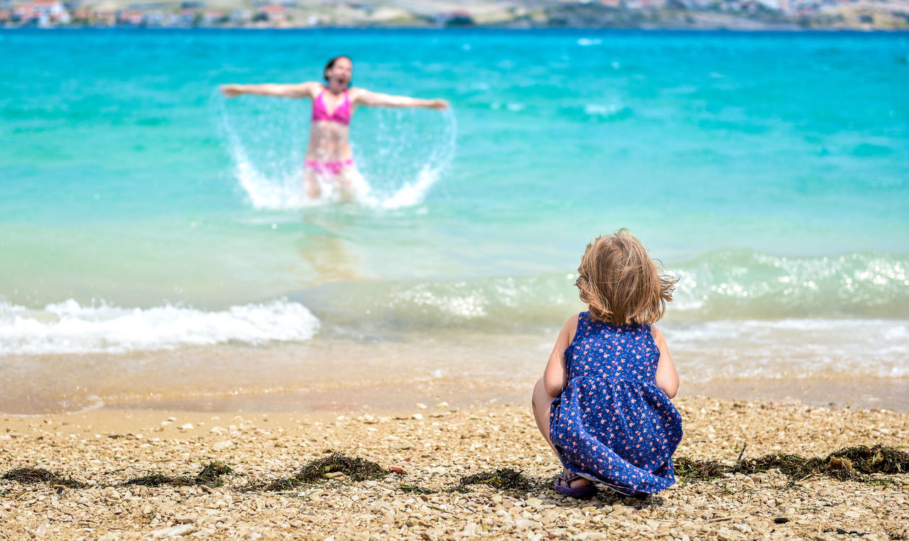 Rear View Of Daughter Looking At Mother Enjoying In Sea