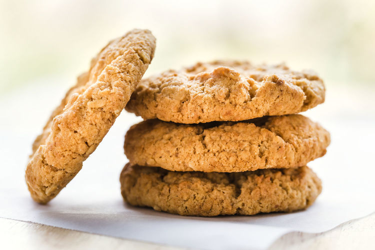 Stack of four crisp ANZAC biscuits on baking paper close-up Anzac Biscuits Australian Cookies Four Freshness Stack Backlit Baked Baking Paper Close-up Cookie Crisp Food Freshness Ready-to-eat Snack Stacked Sweet Sweet Food
