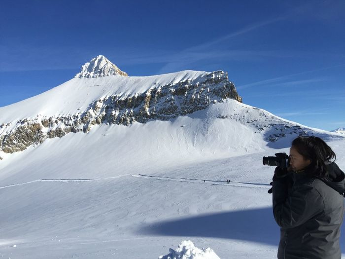 Man photographing snowcapped mountains against sky