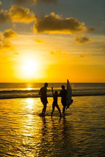 Father And Children Walking On Sea Shore Against Sky During Sunset