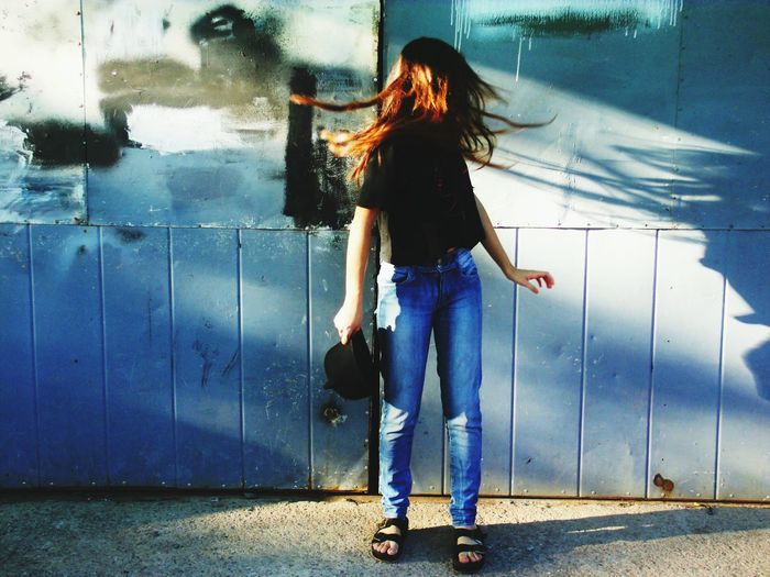 Woman Tossing Hair While Standing Against Gate