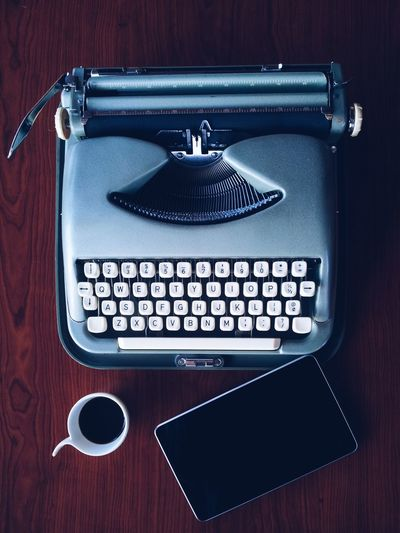 High angle view of typewriter with digital tablet and black coffee on table