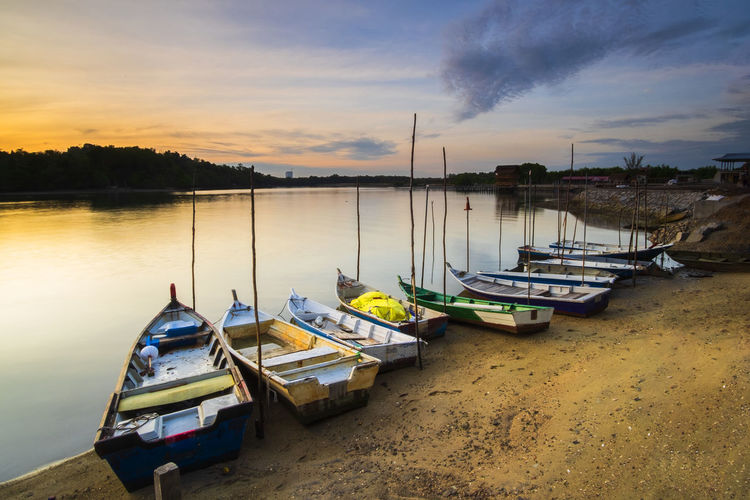 Boats Moored By Lake Against Sky During Sunset